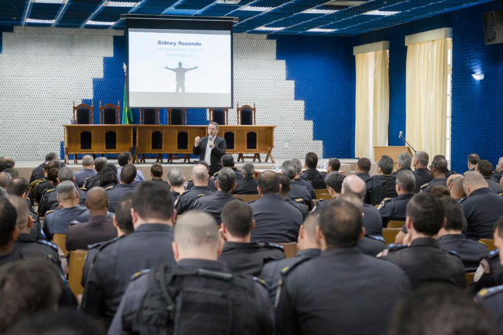 Policiais assistindo a apresentação em auditório